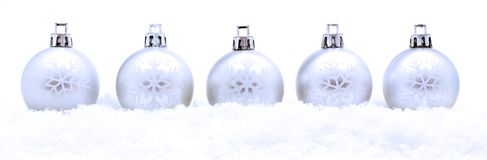 Christmas baubles. Border of silver Christmas baubles in fresh snow Stock Images