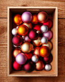 Christmas baubles in box. Overhead view of Christmas balls or baubles in open wooden box with grainy timber background Stock Image