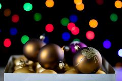 Christmas baubles in a box against a background of Christmas lig Stock Photography