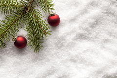 Christmas baubles and branch of spruce tree on snow Royalty Free Stock Images