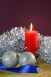 Christmas Baubles and Candle with Tinsel Royalty Free Stock Photography