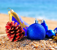 Christmas baubles and cones on sand on beach Stock Photography