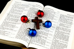 Christmas Baubles and Cross on Bible on Black Background Royalty Free Stock Photo