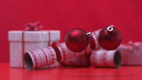 Christmas baubles dropping and bouncing beside crackers and presents. In slow motion
