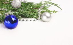 Christmas baubles and evergreen branches on white. stock images