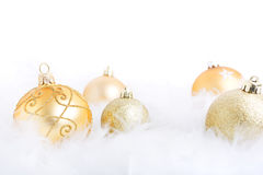 Christmas baubles on a feathery surface, brightly lit. Golden Christmas baubles on a soft feathery surface with a white background Royalty Free Stock Images