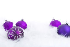 Christmas baubles on a feathery surface, brightly lit. Purple Christmas baubles on a soft feathery surface with a white background Royalty Free Stock Photo