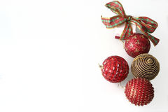 Christmas baubles. Four Christmas baubles red and golden and a box with ribbon in a white background with space to the left Stock Images
