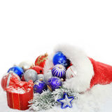 Christmas baubles and gift in santa claus hat Stock Image