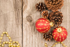 Christmas baubles, golden beads and pine cones top view Stock Photos