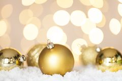 Christmas Baubles on shiny background. Golden Christmas baubles on snow, tree lights background stock photos