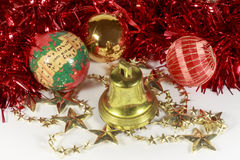Christmas baubles beside golden stars and bell Royalty Free Stock Images