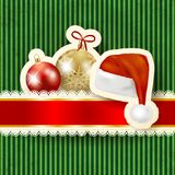 Christmas baubles and hat on cardboard background Royalty Free Stock Image