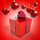 Christmas baubles and hearts with gift box. Over red background Stock Photos