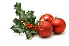 Christmas baubles with holly. Three red Christmas tree decorations with a sprig of holly Royalty Free Stock Photo