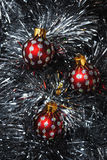 Christmas baubles nesting in silver tinsel. Red and silver Christmas baubles nesting in silver tinsel Stock Image