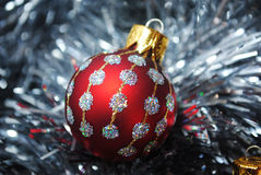 Christmas baubles nesting in silver tinsel. Red and silver Christmas bauble nesting in silver tinsel Royalty Free Stock Photo