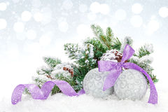 Christmas baubles and purple ribbon over snow bokeh background Royalty Free Stock Images