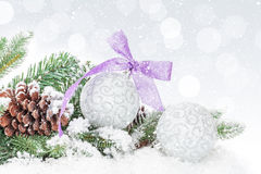 Christmas baubles and purple ribbon over snow bokeh background Stock Photo