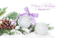 Christmas baubles and purple ribbon with snow fir tree Royalty Free Stock Photo