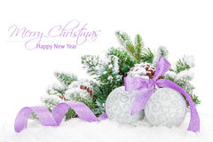 Christmas baubles and purple ribbon with snow fir tree Stock Photos