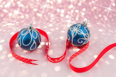 Christmas baubles with red dotted ribbon on bokeh background Stock Images