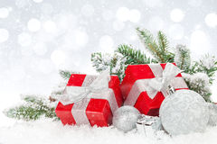 Christmas baubles and red gift boxes over snow bokeh background Stock Image