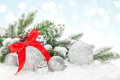 Christmas baubles and red ribbon over snow bokeh background Royalty Free Stock Images