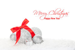 Christmas baubles and red ribbon over snow Stock Photo