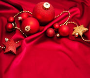 Christmas baubles on the red silk Stock Images