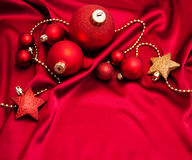 Christmas baubles on the red silk Stock Photo
