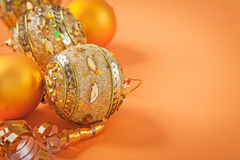 Christmas baubles and ribbon on orange colored background Stock Photography