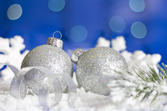 Christmas baubles and silver ribbon on snow Royalty Free Stock Photos