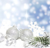 Christmas baubles and silver ribbon on snow stock image