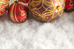 Christmas baubles on snow Royalty Free Stock Images