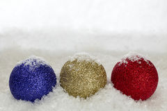 Christmas Baubles Sprinkled With Snow. Flakes against a snow backdrop with copy space Stock Photo
