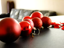 Christmas Baubles on Table. Closeup of Christmas Baubles and Ribbons on the Table in Room Royalty Free Stock Photography