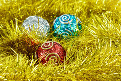 Christmas baubles. Three Christmas baubles or decorations in a bed of tinsel Royalty Free Stock Photography