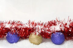 Christmas Baubles Tinsel and Snow. Christmas baubles and tinsel covered in snow with copy space to add your own message Royalty Free Stock Photography