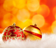 Christmas baubles on white fur and lights Stock Photography