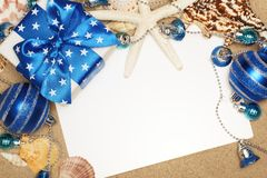 Christmas at the beach. Christmas gifts and blank card on sand beach,closeup Royalty Free Stock Photo