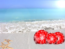 Christmas beach balls. Red Christmas balls on a tropical beach Stock Photo
