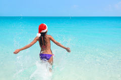 Christmas beach bikini woman swimming in ocean. Beautiful adult entering perfect turquoise water with arms back in freedom feeling free enjoying winter Stock Images