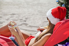 Christmas on the beach girl in santa hat. With a martini glass in hand Royalty Free Stock Photography