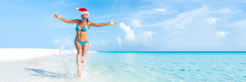 Christmas beach holiday travel banner panorama. Background for Christmas vacation fun. Bikini woman running carefree splashing water enjoying swim caribbean stock photo