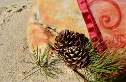 Sandy beach Christmas by the sea natural pine cones red throw. Christmas in beach sand,  rock setting with a pine cone burgundy red organza spiral motive throw Stock Photography