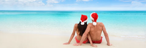 Christmas beach vacation holidays couple banner. Christmas beach vacation holidays santa hat couple relaxing from behind sitting on white sand panorama banner royalty free stock photo