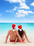 Christmas beach vacation holidays couple relaxing. Beach vacation holidays couple relaxing sitting down on white sand looking at turquoise ocean view in tropical stock photo