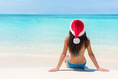 Christmas beach vacation santa claus hat woman. Tropical holiday bikini girl sitting down on white sand at paradise travel destination relaxing on paradise royalty free stock images