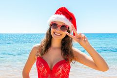 Christmas beach vacation travel portrait woman wearing Santa hat enjoying christmas on tropical beach stock photo